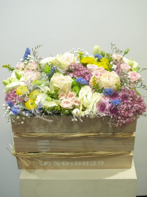 Caja alta madera con flores de temporada variadas. 2